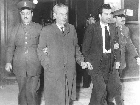 Μπελογιάννης και Καλούμενος οδηγούνται σιδεροδέσμιοι στο δικαστήριο. Θα υπερασπιστούν το Κόμμα, τις αρχές και την ιδεολογία του μέχρι την τελευταία τους πνοή