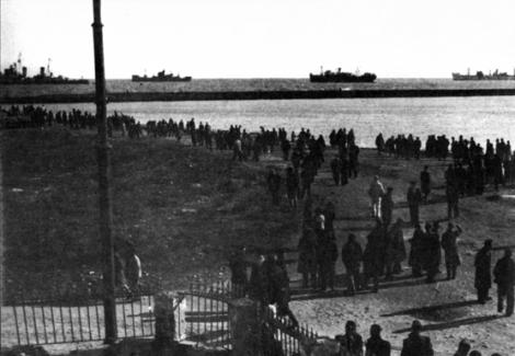 """Ο λαός της Μυτιλήνης κατευθύνεται στα """"Μπλόκια"""". Στο βάθος τα βρετανικά πολεμικά πλοία."""